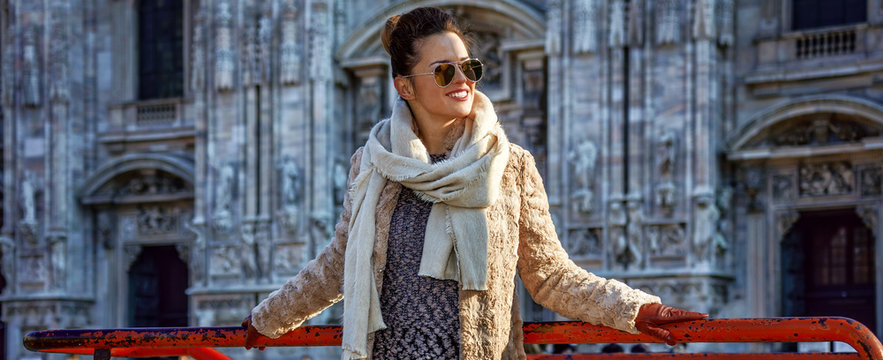 happy woman in front of Duomo in Milan, Italy looking aside