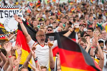 Jubelnder Fußball-Fan mit deutscher Fahne und einem Becher Bier in einer Menge jubelnder Fans beim Public Viewing