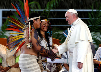 Pope Francis greets members of an indigenous group from the Amazon region, in Puerto Maldonado