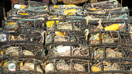 Many Crab cages stacked. Crab traps are used to bait, lure, and catch crabs for commercial or recreational use. Crabbing or crab fishing is the recreational hobby and commercial occupation of fishing.
