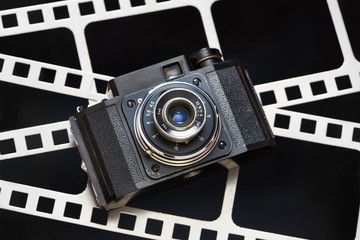Old retro rangefinder camera on background of film perforation