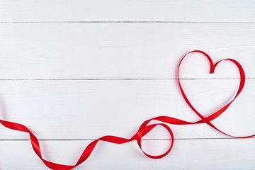Valentines Day background with red ribbon shaped as heart on white wood table, copy space for text. Love, wedding concept. Top view, flat lay