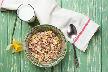 Bowl of oat flakes and glass of milk, on wooden background. Top view.