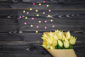 Spring background with bunch of yellow tulip flowers corner and pink heart sprinkles, copy space. Flat lay, top view. Holiday greeting card for Valentine's Day, Woman's Day (March 8), Mother's Day