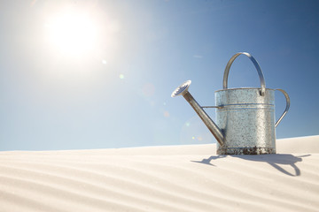 concept watering can on sand dune global warming,water resriction,drought