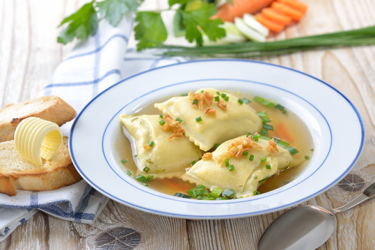 Gemüsebrühe mit deftigen schwäbischen Maultaschen, dazu getoastetes Baguette mit Butterröllchen  - Vegetable soup with Swabian-style ravioli served with butter toast