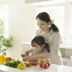 母親に野菜の切り方を教えてもらう女の子