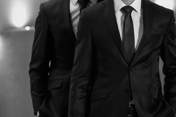 Portrait of two sexy handsome fashion male models men dressed in elegant suits on black studio