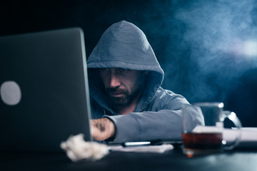 A computer hacker is typing on a laptop in a smoky room. Dark background