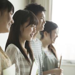 勉強道具を持ち微笑む学生