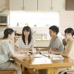 友達の家に集まり勉強をする学生