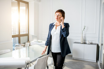 Portrait of an elegant senior businesswoman dressed in the suit talking with phone in the white office