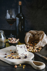 Wensleydale cheese with cranberries, red wine, honey, nuts, raisins on wooden cutting board. Black concrete background. Selective focus.