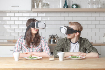 young family couple sittin at the dinner table on kitchen with VR glasses and try to see each other, futuristic concept
