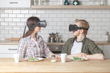 young family couple sittin at the dinner table on kitchen with VR glasses and try to see each other, internet technology concept