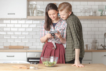 young couple on kitchen making photo of their homemade salad, copy space left