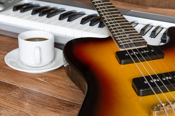 Electro guitar, piano and cap of coffee