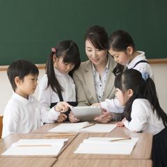 タブレットPCを見る先生と小学生