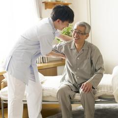 シニア男性を支える介護士