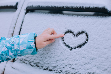 Woman making heart symbol on car window