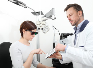 optometrist examining eyesight  woman patient in optician office, stereo test