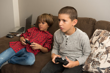 Two happy  young boy friends playing video games, holding remote controlers