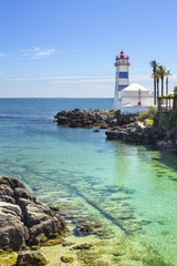 old colored lighthouse with emerald water in sunny day in Portugal