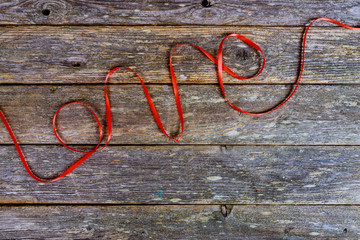 Inscription love from red wool thread on a old wooden