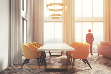 White dining room corner, yellow chairs side man