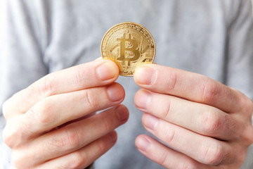 Foto op Plexiglas Bar Cryptocurrency golden bitcoin coin in man hand. Electronic virtual money for web banking and international network payment. Symbol of crypto currency
