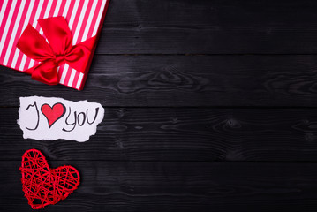 Background Valentines Day and weddings: a gift and a heart on a wooden table top view with copy space.