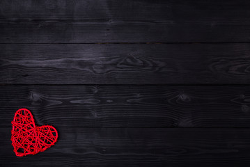 Red heart lies on a wooden black background, top view with copy space.