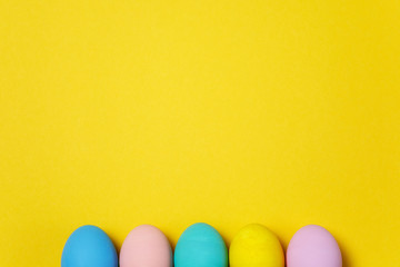 Row of five colorful pastel monophonic painted Easter eggs isolated on yellow background for card or postcard. Happy Easter concept. Copy space for advertisement. With place for text. Top view on eggs