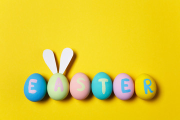 Row of six colorful pastel monophonic painted Easter eggs with inscription Easter, fun bunny ears on egg isolated on yellow background. Copy space for advertisement. With place for text. Top view.