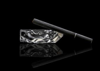 Single Kretek black clove cigarrete on a glass ashtray, black background and reflective surface.