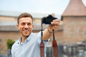 Man Taking Selfie Photos On Camera On Street.