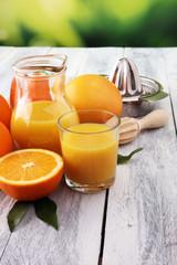 Glass of orange juice and slices of orange fruit on wooden background.