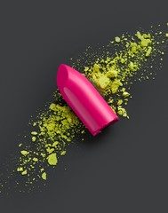 Bright pink lipstick on powdered yellow cosmetics studio shot