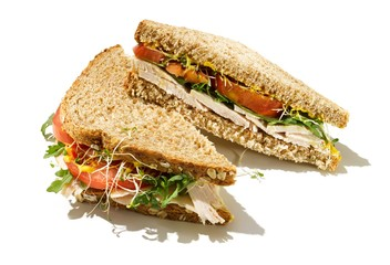 Sliced chicken sandwich with wheat bread on white background