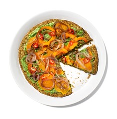 Plate of sliced vegetable pizza with pesto sauce