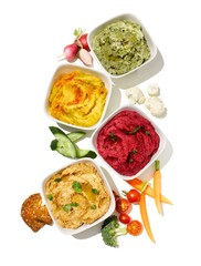 Bowls of hummus and vegetable dips with fresh vegetables on white background