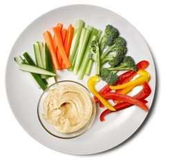 Plate of fresh vegetable slices and hummus on white background
