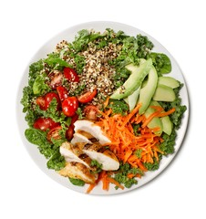 Kale and quinoa salad with chicken, avocado and tomato slices on white background
