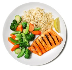 Plate of grilled salmon with cooked vegetables and rice on white background