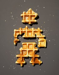 Waffle pieces shaped like a person on gray background