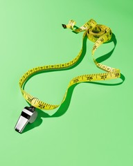 Measuring tape with whistle on green background studio shot