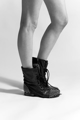 Legs of a young woman wearing studded black boots