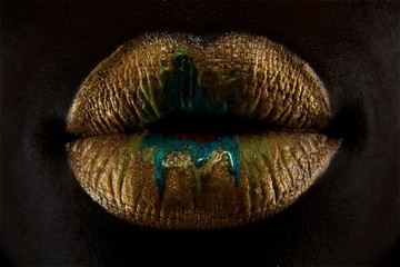 Close-up of woman's lips with gold lipstick