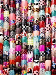 Colorful pile of artificial fingernails with vibrant nail wrap patterns