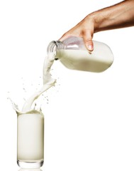 Man pouring bottle of milk into overflowing glass against white background